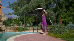 Leggy young sexy girl walking along the pool with clean blue water at resort  Stock Footage