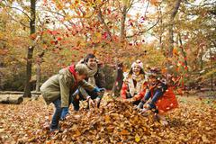 Stock Photo of Family playing in autumn leaves