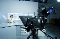 young anchorwoman at TV studio - stock photo