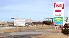 Petrol / gas station with busy road in background with blue sky Stock Footage