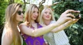 Three young blonde sexy rave girls make selfie photo for instagram in a park Footage