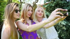 Three young blonde sexy rave girls make selfie photo for instagram in a park Stock Footage