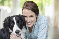 Smiling woman petting dog indoors - stock photo