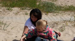 Girl playing on the sand and explaining something to mom Stock Footage