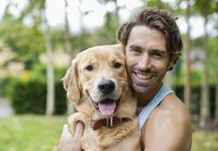 Smiling man petting dog outdoors - stock photo