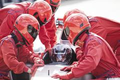 Racing team working at pit stop - stock photo