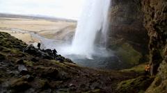 behind waterfall selialandsfoo in iceland spring time with rocks water splashing - stock footage