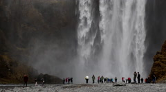 Skogafoss waterfall in iceland with tourists at bottom Stock Footage