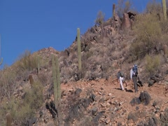 Men Hiking up Desert Mountain Stock Footage