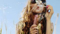 SLOW MOTION: Young woman blowing soap bubbles Stock Footage