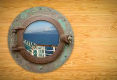 Antique Porthole on Bamboo Wall with View of Ship Deck Railing and Ocean Stock Photos