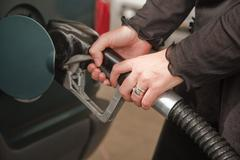 Woman's Hands Pumping Gasoline at the Service Station. - stock photo