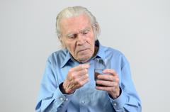 Senior man taking the prescribed dose of medicine - stock photo