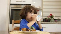 Child eating yummy cake and drinking milk. - stock footage
