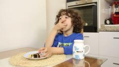 Child eating yummy cake and drinking milk. Stock Footage