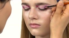 Makeup artist apply make-up for girl, eyeshadow, using eye shadow brush, color Stock Footage