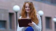 Beautiful young girl with plush red hair using a tablet computer Stock Footage