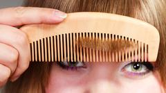 Closeup woman combing her fringe with comb - stock photo