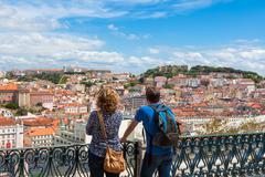 Tourist watching to Lisbon rooftop from Sao Pedro de Alcantara viewpoint - Mi Stock Photos