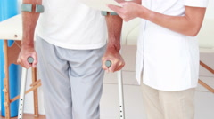 Doctor showing clipboard to her patient with crutch Stock Footage