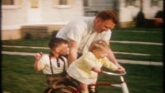 2145 - dad pushes the kids around on the bike - vintage film home movie Stock Footage