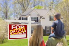Curious Family Facing Sold For Sale Real Estate Sign and Beautiful New House. Stock Photos