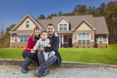 Stock Photo of Happy Mixed Race Family in Front of Their Beautiful New Home.