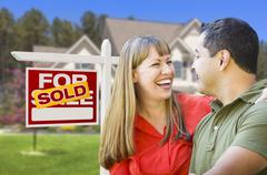 Couple in Front of Sold Real Estate Sign and House Stock Photos