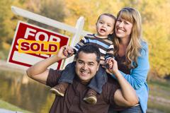 Happy Mixed Race Couple with Baby in Front of Sold Real Estate Sign. - stock photo