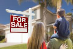 Curious Family Facing For Sale Real Estate Sign and Beautiful New House. - stock photo