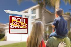 Curious Family Facing Sold For Sale Real Estate Sign and Beautiful New House. - stock photo