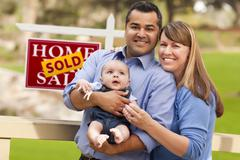 Happy Mixed Race Couple with Baby in Front of Sold Real Estate Sign. Stock Photos