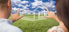 Dreaming Couple Framing Hands Around Ghosted House Figure in Grass Field. Stock Photos