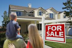 Stock Photo of Family Looking at New Home with For Sale Sign