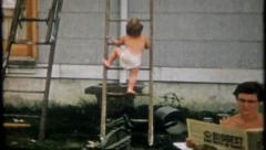2146 - children try to climb ladder to help dad - vintage film home movie Stock Footage