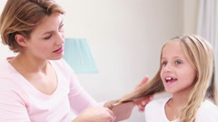 Stock Video Footage of Smiling mother combing hair of daughter