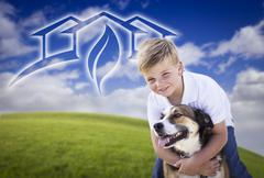 Boy and His Dog Playing Outside with Ghosted Green House Graphic Above - stock photo