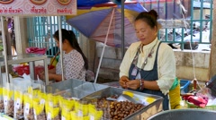 Woman sells Sweet Chestnuts at Market in Thailand Stock Footage
