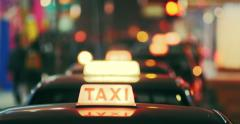 Taxi cabs at night time on city street with defocused lights. Hong Kong downtown Stock Footage