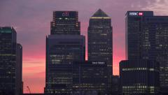 Zoom out, Canary Wharf skyline at sunset, London, England - stock footage