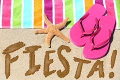Beach party fiesta travel fun concept - FIESTA written in sand - stock photo