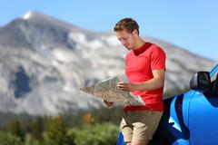 Driver man looking at map by car in Yosemite Park - stock photo