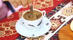 A person using a spoon to stir a coffee drink in Turkey - stock footage