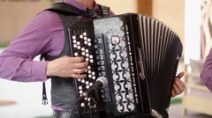 Musician hand playing accordion closeup in dramatic shadows Stock Footage