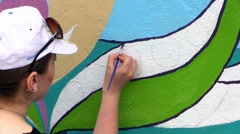 Girl drawing on the wall,mural art. - stock footage