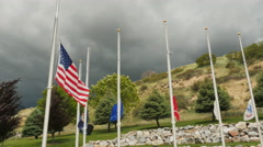 American flag & flags of military branches fly half mast against dark gray sky Stock Footage