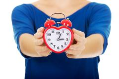 Young woman holding alarmclock. Stock Photos