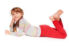 Stock Photo of Side view of smiling child girl lying on stomach
