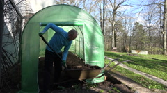 Gardener man unload rotten compost to greenhouse from barrow. 4K Stock Footage