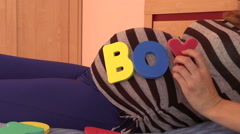 Pregnant woman pick word boy from toy letters on her stomach Stock Footage